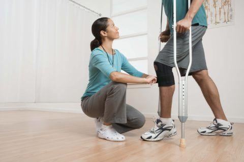 Пациента обучают ходьбе с поддерживающими средствами
