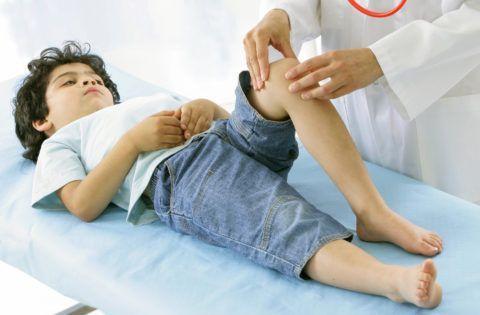 Пальпация суставов колена ортопедом у мальчика четырёх лет.